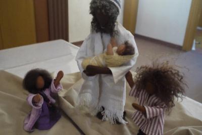 Mit biblischen Erzählfiguren werden die folgenden Szenen dargestellt. Hier: Jesus hält ein Baby im Arm, 2 weitere Kinder stehen neben ihm