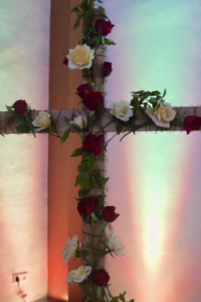 Das Holzkreuz ist mit roten und weißen Rosen geschmückt