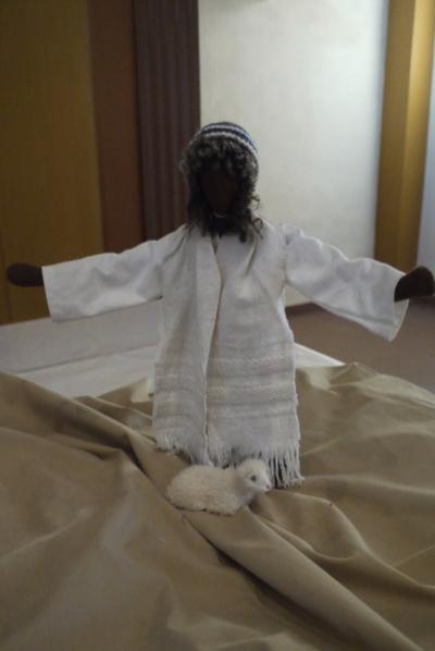 Jesus steht mit weit geöffneten Armen da, zu seinen Füßen ein Lamm