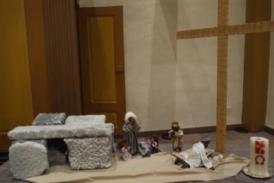 links steht aus Steinen das  Grab. Rechts stehen Jesu Jünger  verzweifelt unter dem leeren Kreuz